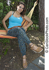 beautiful young woman sitting in a hammock