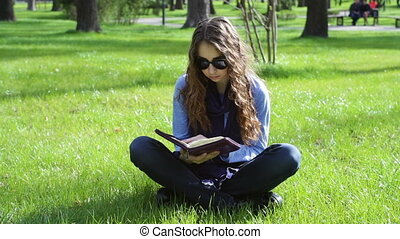 beautiful young woman sitting in a summer park on the grass and reading a book of the Bible