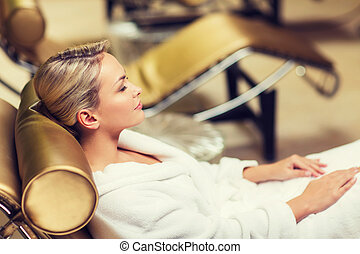 beautiful young woman sitting in bath robe at spa - people,...
