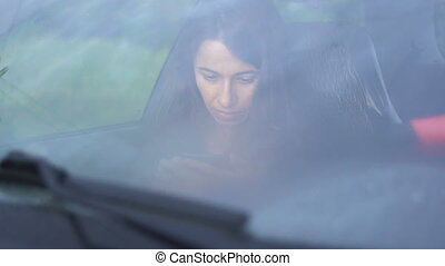 Beautiful young woman sitting in car with smartphone
