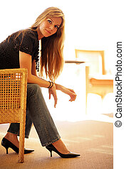 Beautiful young woman sitting in chair