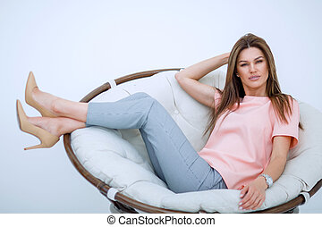 beautiful young woman sitting in comfortable chair.