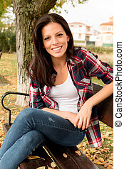 Beautiful young woman sitting in park at fall