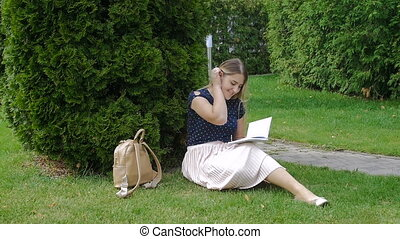 Beautiful young woman sitting in park on grass and writing a diary. Slow motion footage