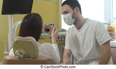 Beautiful young woman sitting in the dental chair in the clinic. the doctor examines the oral cavity. Woman smiling. Through the mirror shot.