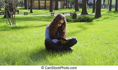 beautiful young woman sitting in the park on the grass and reading a book