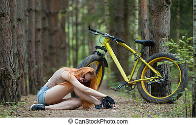 Beautiful young woman sitting in the woods with fat bike