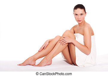 Beautiful young woman sitting in white towel