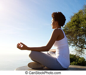 Beautiful young woman sitting in yoga pose at beach