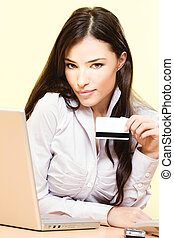 Beautiful young woman sitting near laptop and mobile phone holding credit card in her left hand
