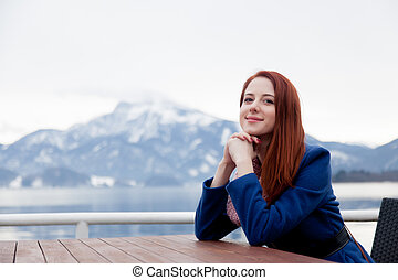 beautiful young woman sitting near table on the mountains background