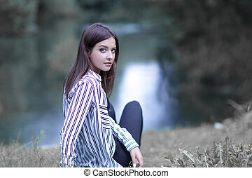 young woman sitting near the river