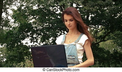 beautiful young woman sitting near trees with a laptop and her hair fly