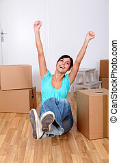 Beautiful young woman sitting next to boxes in new house