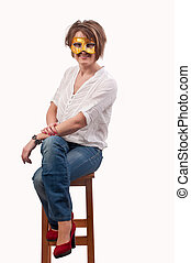 beautiful young woman sitting on a chair with carnival mask