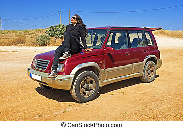 Beautiful young woman sitting on a jeep in the desert
