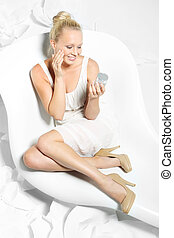Beautiful young woman sitting on a white