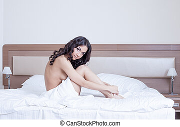 Beautiful young woman sitting on bed