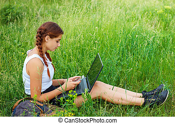 beautiful young woman sitting on grass with laptop