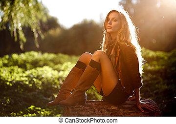 Beautiful Young Woman sitting on log posing