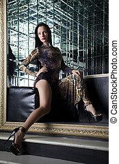 Beautiful young woman sitting on sofa in nightclub