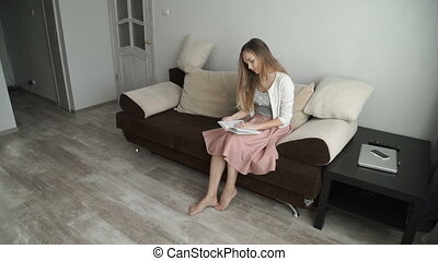 Beautiful young woman sitting on sofa reading book and smiling