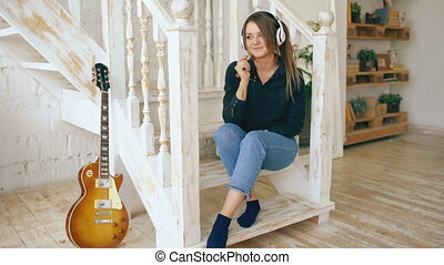 Beautiful young woman sitting on stairs listen music in headphones at home indoors
