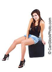 Beautiful young woman sitting on stool