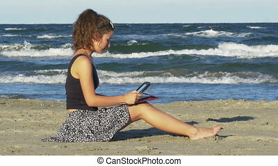 Beautiful young woman sitting on the beach and tipping on her tablet pc on a summer day