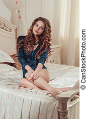 Beautiful young woman sitting on the bed