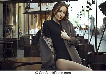 Beautiful young  woman sitting on the desk