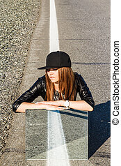 Beautiful young woman sitting on the road