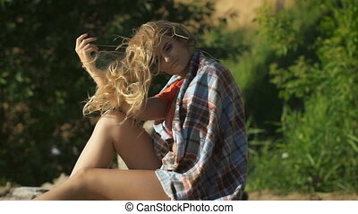Beautiful young woman sitting on the beach at a river in the blanket and touching her hair