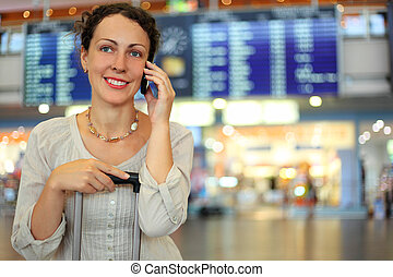 beautiful young woman sitting on their luggage in hall of airport and talking by mobile phone