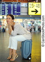 beautiful young woman sitting on their luggage in hall of airport and waiting airplane