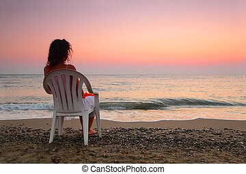 beautiful young woman sitting on white plastic chair on beach and watching sunset, shallow depth of Focus