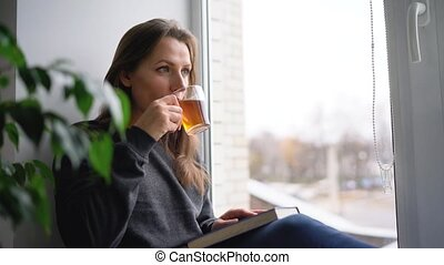 Beautiful young woman sitting on window sill with tea and reading book