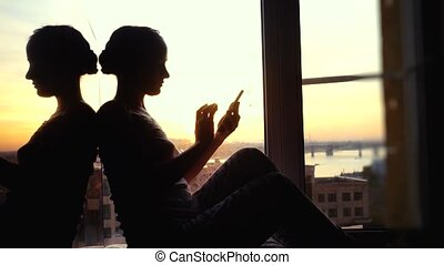 beautiful young woman sitting on window uses smart phone drinks coffee on background of the sunset and city. 3840x2160