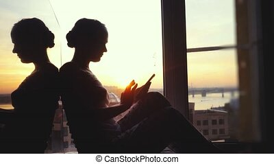 beautiful young woman sitting on window uses smart phone on background of the sunset and city. 3840x2160