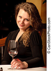 Beautiful young woman sitting with a wineglass in the restaurant