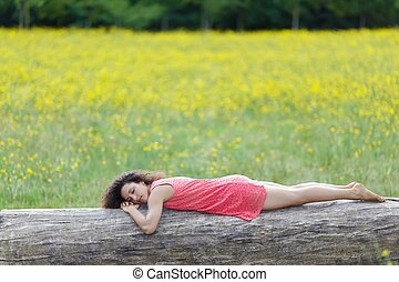 Beautiful young woman sleeping on a log or tree trunk in a...
