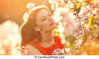 Beautiful young woman smelling a flowering branch of a tree.