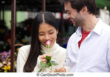 Beautiful young woman smelling rose with boyfriend smiling