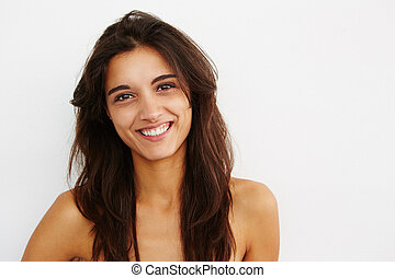 beautiful young woman smiling against while wall