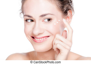 Beautiful young woman smiling and putting eye cream.