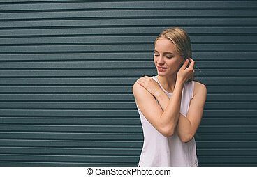 Beautiful young woman smiling and standing with crossed arms against gray wall