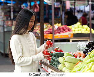 Beautiful young woman smiling at the vegetable market