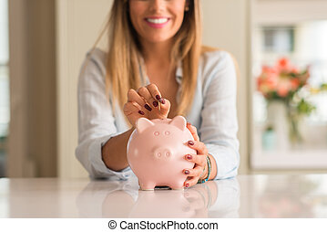 Beautiful young woman smiling holding a coin investing in to a piggy bank at home. Business concept.