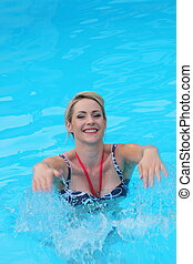 Beautiful young woman smiling in a swimming pool,