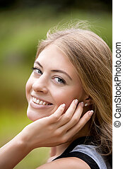 Beautiful young woman smiling, outdoor portrait